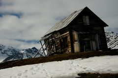 Rickety hut on ridge with mountains behind Stock Photography
