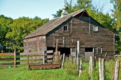 Rickety Old Barn in the Pasture. A rickety old weathered barn is missing several doors Royalty Free Stock Images