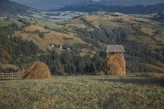 2 ricks сена в сельской местности с горами Стоковое Изображение