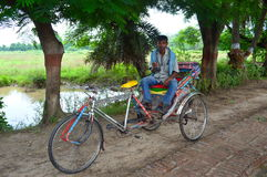 Ricksaw puller in India. Rickshaw puller relaxing alongside a road in Indian Village Stock Photos