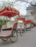 Rickshaw's parkerar i ottan runt om det berömda Klocka tornet, Peking, Kina arkivfoton