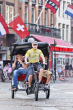 Rickshaw at Amsterdam Dam square. AMSTERDAM-AUG. 19. Rickshaw at Dam square. 38% of traffic movement in Amsterdam is by bike, 37% by car, 25% by public Royalty Free Stock Photos