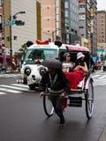 Rickshaw @ Asakusa , Tokyo, Japan. Traditional rickshaw being pushed down the busy roads of Asakusa. Only in Japan will you see a Panda bus and a rickshaw next Royalty Free Stock Photo