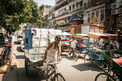 Rickshaw carrying heavy cargo on the street of Old Delhi, India Royalty Free Stock Photo