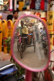 Rickshaw driver. In India reflected in a motorbike's mirror Royalty Free Stock Photography