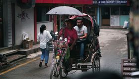 Rickshaw Driver Brings Passenger Passing Thamel Street. Editorial royalty free stock photos