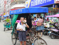 Rickshaw driver drinking water. Tricycle in longhai city, china. in some less developed cities, manpower tricycle is a common means of transport Royalty Free Stock Images