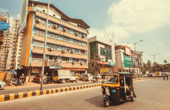 Rickshaw driving past colorful modern buildings on indian street Royalty Free Stock Photography