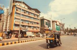 Rickshaw driving past colorful modern buildings on indian street. MANGALORE, INDIA - FEB 24: Rickshaw driving past colorful modern buildings on indian street on Royalty Free Stock Photography