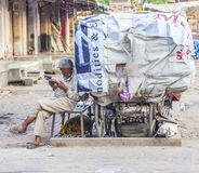 Rickshaw man rests and reads news Stock Image