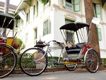 Rickshaw. Old vintage retro human power cute rickshaw, vechicle of the past as tourist attraction today, at historical colonial style house: KHUM CHAO LUANG, in Royalty Free Stock Photos