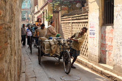 Rickshaw-puller carrying goods on the road of Kolkata Stock Photo