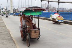 Rickshaw pullers ride manpower tricycle on jingjiang bridge. Old tricycle in longhai city, china. in some less developed cities, manpower tricycle is a common Stock Photography