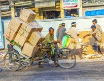 Rickshaw rider transports heavy Royalty Free Stock Photos