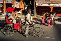 Rickshaw rider transports passenger Royalty Free Stock Images