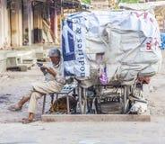 Rickshawmannen vilar och läser nyheterna Fotografering för Bildbyråer