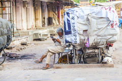 Rickshawmannen vilar och läser nyheterna Arkivbild