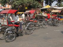 Rickshaws and their passengers Stock Images