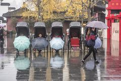 The rickshaws waiting for guests on the Confucius Temple market in the early winter and rainy days. In the early winter and rainy days, the rickshaw driver royalty free stock images