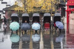 The rickshaws waiting for guests on the Confucius Temple market in the early winter and rainy days. In the early winter and rainy days, the rickshaw driver stock image