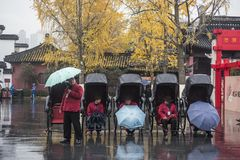 The rickshaws waiting for guests on the Confucius Temple market in the early winter and rainy days. In the early winter and rainy days, the rickshaw driver stock photo