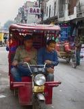 Rickshawtaxichauffören på elektrisk tuk-tuk bär passagerare Fotografering för Bildbyråer