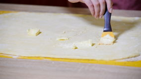 Ricoprendo la pasta di burro e spazzola Fabbricazione dei rulli di cannella archivi video