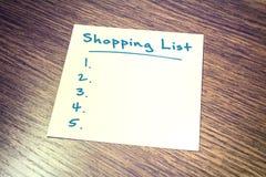 Ricordo in bianco della lista di acquisto su carta che si trova sull'armadietto di legno Immagine Stock