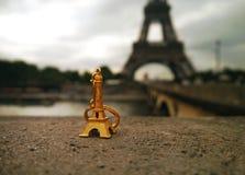 Ricordo dorato - una torre Eiffel miniatura davanti alla cosa vera Immagine Stock