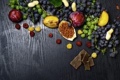 ricos con resveratrol, uvas, ciruelos, goji, cacahuetes, arándano, chocolate de la comida de los raspberrys en fondo de madera ne imagen de archivo libre de regalías