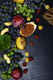 ricos con resveratrol, uvas, ciruelos, goji, cacahuetes, arándano, chocolate de la comida de los raspberrys en fondo de madera ne foto de archivo