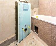 Ricostruzione non finita del bagno o della toilette con le piastrelle di ceramica installate sulle pareti, posto per il lavabo e  fotografia stock libera da diritti