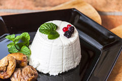 Ricotta cheese with berries, dried figs and some leaves of green fresh mint. Ricotta cheese with berries and dried figs and some leaves of green fresh mint Stock Photo