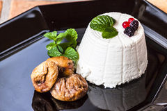 Ricotta cheese with berries, dried figs and some leaves of green fresh mint. Ricotta cheese with berries and dried figs and some leaves of green fresh mint royalty free stock photography