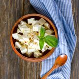 Ricotta cheese cubes in a wooden plate, top view stock image
