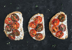 Ricotta and cherry-tomato sandwiches with fresh thyme over a dar Royalty Free Stock Image