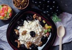 Ricotta e prugne su una banda nera Frutti canditi, uva passa in una scatola di legno C'è un cucchiaio di legno vicino immagine stock