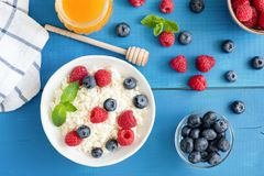 Ricotta with fresh berries and honey on blue table. Cottage cheese, curd cheese or tvorog with berries in bowl. Summer dessert, breakfast or healthy snack Stock Photos
