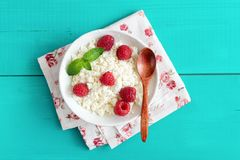 Ricotta with raspberries in a bowl. On turquoise wooden background. Curd cheese, cottage cheese, tvorog. Healthy eating, healthy lifestyle, summer dessert or Stock Images