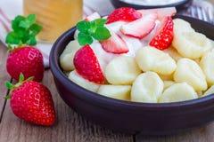 Ricotta russa e ucraina tradizionale & x22; lazy& x22; gli gnocchi sono servito con yogurt, miele e la fragola fotografia stock