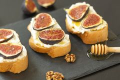 Ricotta sandwiches, fresh figs, walnuts and honey on a slate plate royalty free stock photo