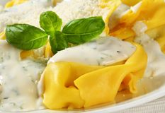 Ricotta and spinach tortelloni with cream sauce and Parmesan Stock Photo