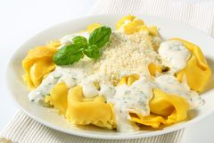 Ricotta and spinach tortelloni with cream sauce and Parmesan Royalty Free Stock Photography