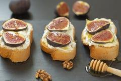 Ricottasmörgåsar, nya fikonträd, valnötter och honung på en kritiseraplatta arkivbild