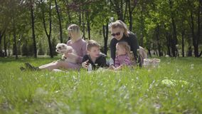 Ricreazione all'aperto della famiglia piacevole del ritratto Due belle giovani madri ed i loro bambini ad un picnic nel parco un  stock footage