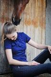 Rid- flicka och häst i stall Arkivfoto