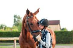 Rid- ung tonårs- flicka kyssa hennes kastanjebruna häst arkivbild