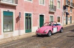 Rida en rosa VW-skalbagge i Lissabon arkivbilder