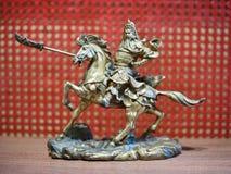 Riddare på hästryggminiatyren Metallisk riddare som rymmer ett svärd på baksidan av en häst Arkivbilder
