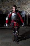 Ridder in Armor With Sword Standing in Oude Kerk en het Bekijken Camera Stock Foto